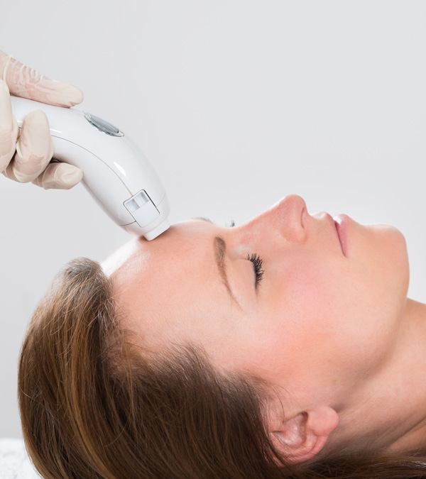 Young Woman Receiving Laser Hair Removal Treatment At Beauty Center
